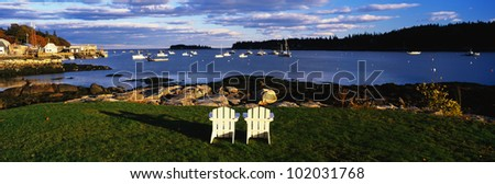 This is an image of two white lawn chairs facing toward the nearby harbor. - stock photo