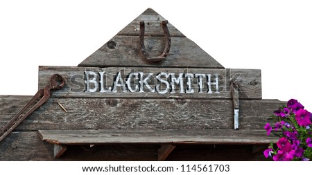 This is an old sign with word blacksmith on rustic wood boards and rusty old vintage tools.  Purple petunia flowers add a splash of color.  Isolated on a white background.