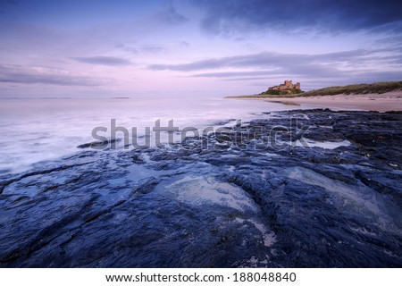 This is Bamburgh Castle in Northumberland, England. The Farne Islands are visible on the horizon.  - stock photo