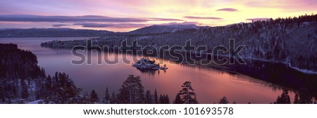 This is Emerald Bay at sunrise after a winter snow storm. There is snow on the land surrounding the bay. - stock photo