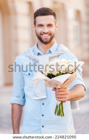 This is for you! Handsome young man holding bouquet of flowers while walking by the street  - stock photo