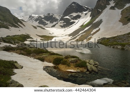 This is gloomy lake in Caucasus mountains in summer - stock photo