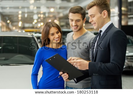This is good choice. Confident young salesman explaining all the car features to the young attractive owners - stock photo