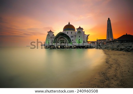 This is image of Malacca Straits Mosque (Masjid Selat Melaka) during sunset. It is located at Malacca , Malaysia and also located in the Strait of Malacca, where it is a busy route in the world . - stock photo