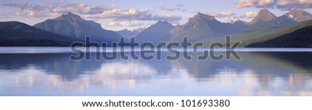 This is Lake McDonald. The surrounding mountains are reflected in the lake. - stock photo