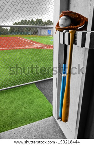 This is looking from the dugout towards home base across the artificial turf. A baseball mitt, softball, and a couple of bats are near the entrance. The clouds are coming and might be rained out. - stock photo