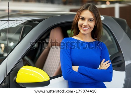 This is my new car. Attractive young woman standing near her new car at the dealership - stock photo