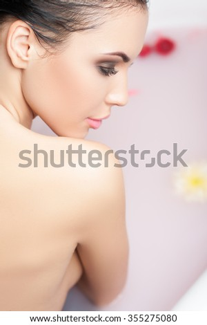 This is my pleasure. Attractive young girl is taking a bathtub. She is sitting and looking down with enjoyment - stock photo