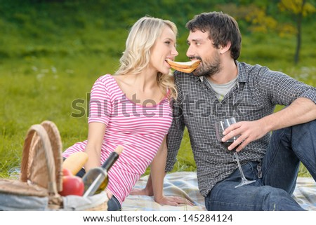 This is my sandwich! Loving young couple holding the only sanwich by their teeth - stock photo