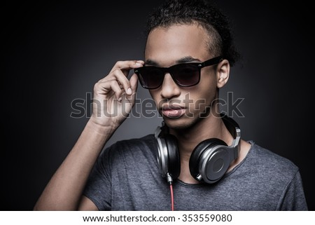 This is my style. Portrait of young African man adjusting his sunglasses and wearing headphones while standing against black background - stock photo