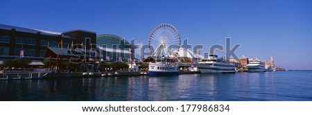 This is Navy Pier with its working Ferris wheel and summer tour boats docked next to it in Lake Michigan.  - stock photo