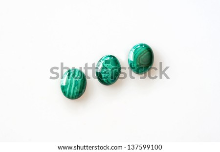 This is 3 oval shaped malachite gems, isolated on a light background.   It is a copper carbonate hydroxide mineral noted by its green bands, placed in a diagonal row.