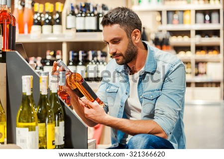 This is perfect wine! Handsome young man holding bottle of wine while standing in a wine store  - stock photo