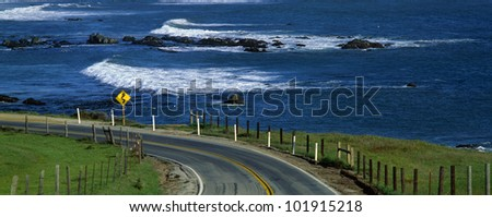 This is Route 1, also known as the Pacific Coast Highway. The ocean is to the right of the road which curves around a bend. - stock photo