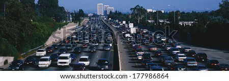 This is rush hour traffic on the 405 Freeway at sunset. There are 10 lanes of traffic total showing both sides of the freeway. There are cars stopped in every lane. - stock photo