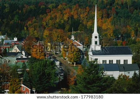 This is Scenic Route 100 in the autumn. There is a large white New England style church with a tall steeple next to smaller buildings of the town.  - stock photo