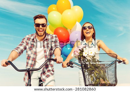 This is so much fun! Low angle view of cheerful young couple smiling and riding on bicycles with colorful balloons in the background - stock photo