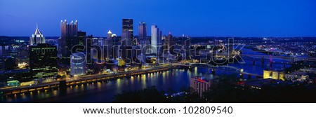 This is the Allegheny and Monongahela Rivers where they meet the Ohio River at dusk. The skyline of Pittsburgh stands behind it. - stock photo