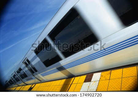 This is the Bart Metro Rail. It is the Bay area rapid transit system. The train is shown at an angle with the end of the train getting smaller into infinity next to a tile floor platform. - stock photo