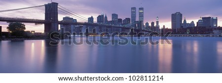 This is the Brooklyn Bridge over the East River with the Manhattan skyline at dusk. The lights of the city are starting to come on. - stock photo