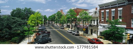 This is the Eastern Shore of Maryland. It typifies small town America or Main Street USA. We see shop fronts on a tree lined street. Cars  are parked in front of shops on either side of the street. - stock photo