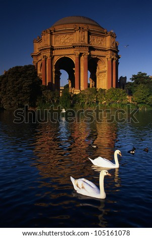 This is the Exploratorium & Science Museum in morning light. There are swans swimming on the pond in front of the museum. - stock photo