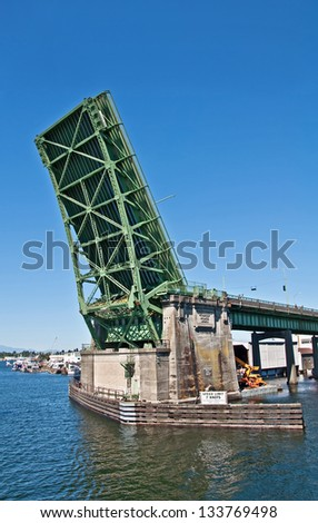 This is the Fremont drawbridge in Seattle, WA, lifted up from Lake Union perspective.  It's a steel double-leaf bascule bridge that is a major transportation object in the region. - stock photo