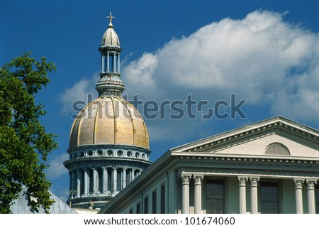 This is the historic State Capitol building in New Jersey. It has a yellow dome and columns making up the structure. - stock photo