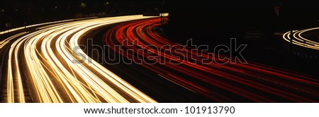 This is the Hollywood Freeway at night. There are the streaked lights from cars on the freeway. - stock photo