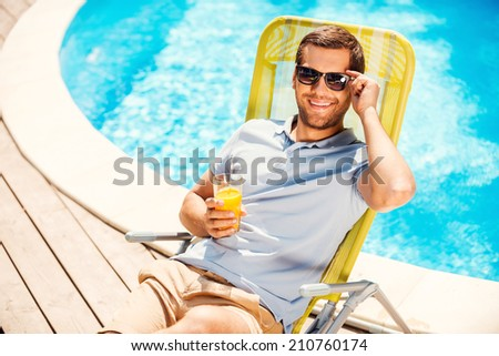 This is the life! Top view of cheerful young man in polo shirt sitting at the deck chair and holding glass with orange juice - stock photo