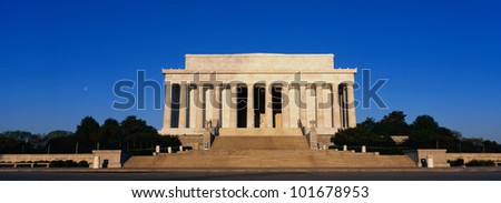 This is the Lincoln Memorial in morning light. We see the wide steps leading up to the columns of the Memorial against a blue sky.