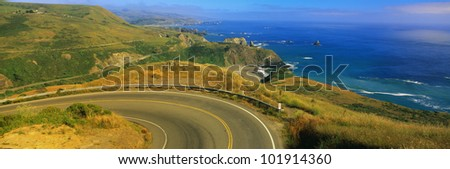 This is the Pacific Coast Highway. The road curves around a bend to the left and drops down overlooking the ocean. The rocky hillside is also seen next to the ocean. - stock photo