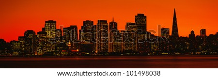 This is the skyline of San Francisco at sunset. There is an orange glow in the sky. - stock photo