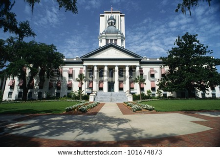 This is the State Capitol building in Florida. It has a large concrete stairway leading up to it with large columns holding up the facade.