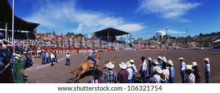 This is the 75th Ellensburg Rodeo that took place on Labor Day, 1997. The Rodeo has taken place from 1923 to the present. It shows a rider on horseback with a lasso riding into the rink after a steer. - stock photo