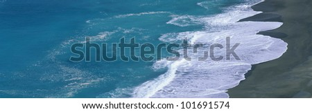 This is the turquoise water of the Pacific Ocean sweeping onto the beach beneath the Pacific Coast Highway. - stock photo