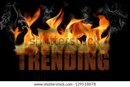 This is the word trending in fire text with billows of smoke rolling off the flame and the word is cracked.  Horizontal on a black background. - stock photo