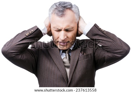 This is too loud! Frustrated mature man in formalwear holding head in hands and keeping eyes closed while standing against white background - stock photo