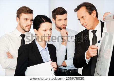 This is very important! Confident mature businessman pointing a graph on whiteboard while his colleagues standing near him and looking at sketch - stock photo