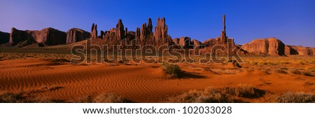 This is Yei Bi Chei and The Totem Pole at sunrise. In front are the sand dunes of Monument Valley. - stock photo