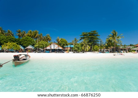 This island paradise possesses the natural beauty of a truly white sand beach with luxury resorts and shallow crystal clear ocean on Ko Lipe, Thailand seen from an offshore perspective - stock photo