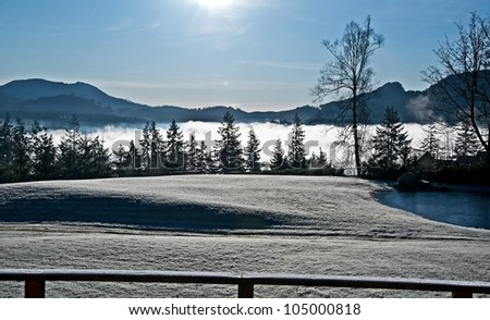 This landscape is a frosty winter morning with heavy fog coming up over a valley, the grass is white with frost.  The pond is frozen over and otherwise a clear, cold, crisp day.