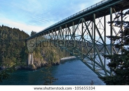 This large steel bridge is over treacherous channel water in this landscape image of Deception Pass, located in Island County, Washington State, America. - stock photo