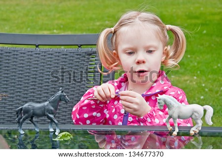 This little 4 year old toddler girl is playing with toy horses in an imaginative game outdoors.  She has blond hair, blue eyes, is Caucasian with pony tails.  She's wearing a pink polka dot raincoat. - stock photo