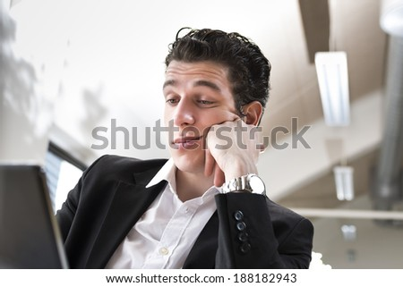 This male business employee is bored in front of his computer. Realistic and authentic situation at every office. Mediterranean and asian facial features