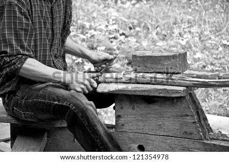 This man is using a pioneer draw knife on wood, used to remove bark from timber in this vintage, black and white lifestyle image. - stock photo