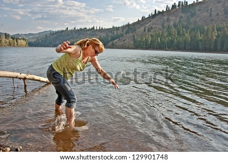 This middle aged woman is barefoot in the water of a lake and skipping rocks.  She is in her fifties, with blond hair pulled back in a pony tail and jeans rolled up. - stock photo