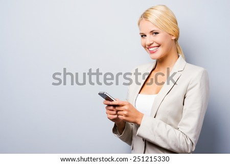 This mobile phone is for smart people. Beautiful young businesswoman holding mobile phone and looking at camera while standing against grey background - stock photo