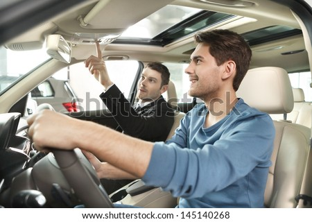 This model comes with added features. Handsome young salesman showing all the car features to the customer - stock photo