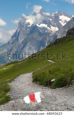 This mountain trail - the Eiger trail in the Swiss Alps - is clearly marked with a white and red stone. In the back the Wetterhorn above Grindelwald. - stock photo
